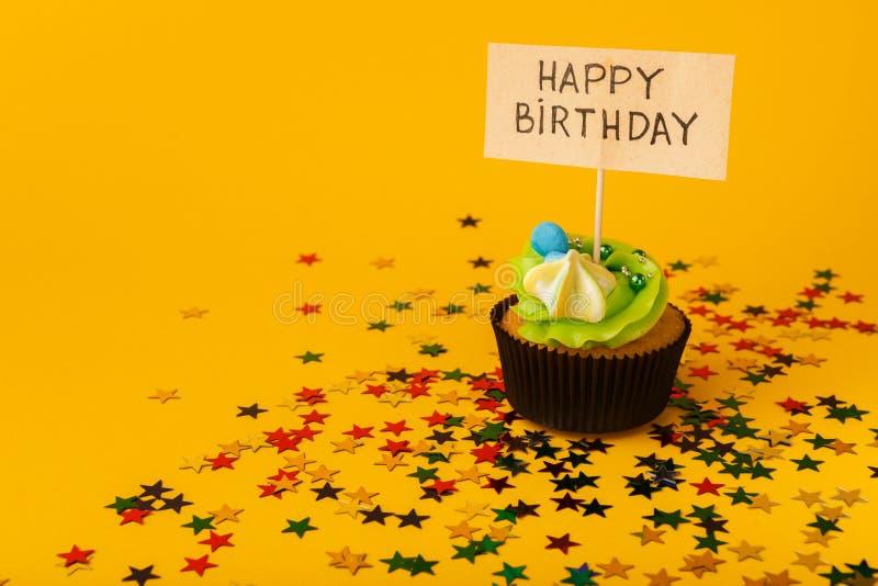 Födelsedagmuffin med hälsningkortet på gul bakgrund arkivbild