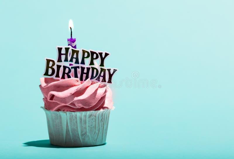 Födelsedagmuffin med stearinljuset på en blå bakgrund royaltyfri foto