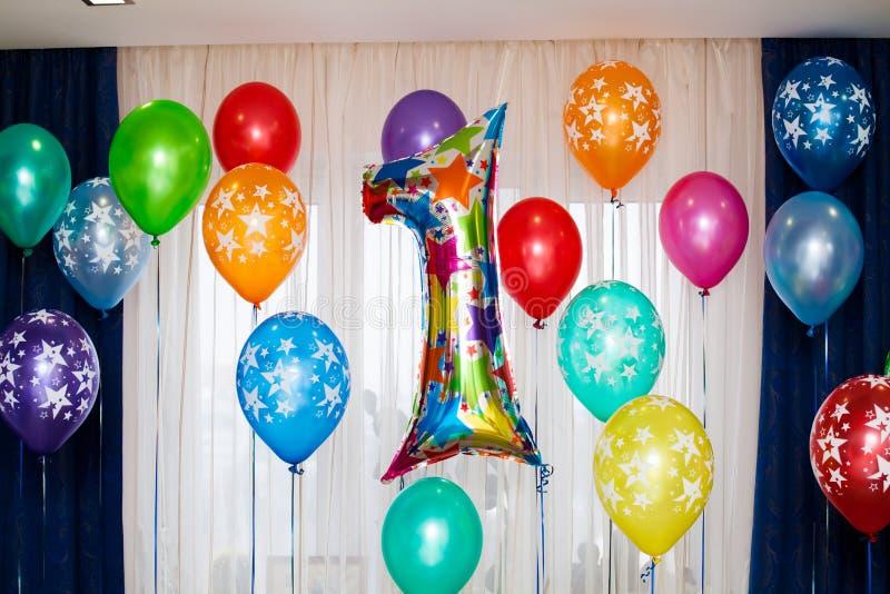 Födelsedagparti, ett årsballongtecken och många färgrika ballonger royaltyfria foton