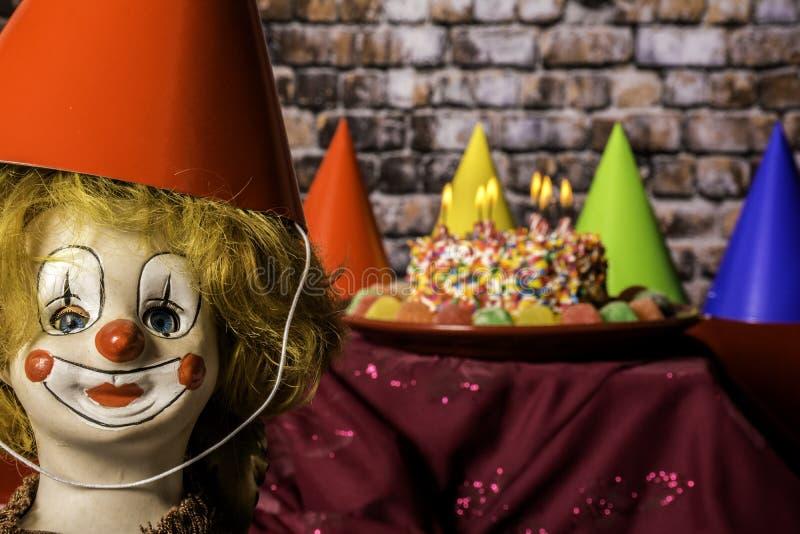 Födelsedagparti med kakan och clownen royaltyfri foto