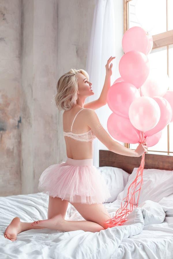Födelsedagpreesnt, ung kvinna på den bärande behån för säng och kjol som spelar med lyckliga ballonger arkivfoto