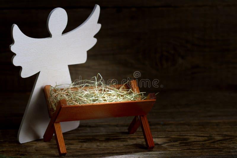 Födelsen av Jesus Christ den abstrakta juljulkrubban med krubban och ängel arkivfoto