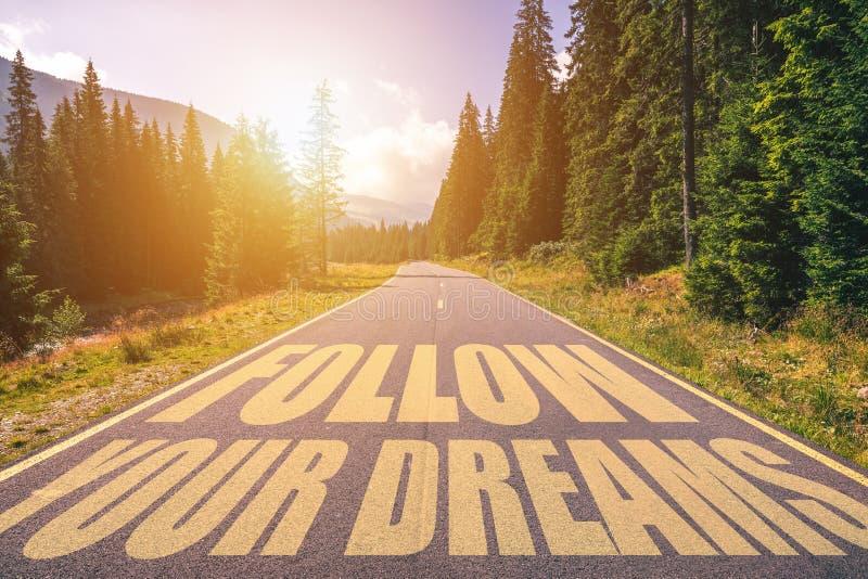 Följ din drömtext som är skriftlig på vägen i bergen royaltyfria bilder