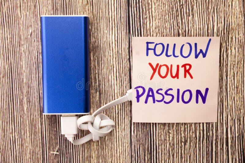 Följ din passion visas på ett anmärkningspapper i olika färger Maktapparaten av blått färgar med vit kabel på träbackgrou royaltyfri bild