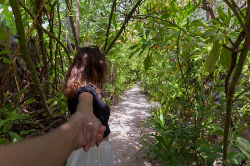 Följ mig begreppet av den unga kvinnan som går på en bana som omges av grön vegetation royaltyfria foton