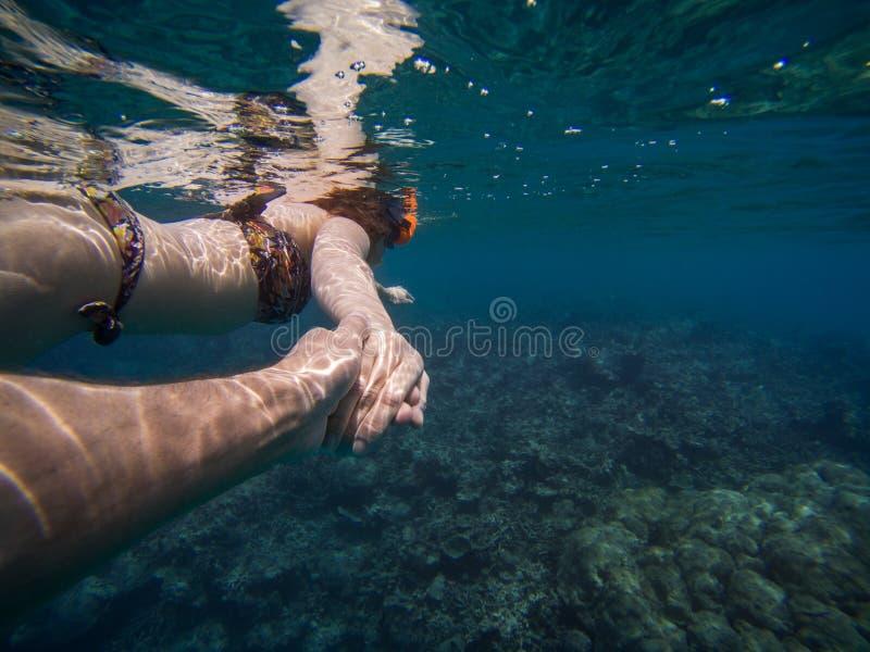 Följ mig begreppet av ett ungt par som snorklar i havet bl?tt klart vatten arkivbilder