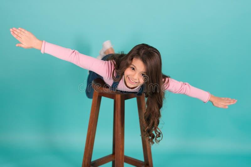 Följ mig Den gladlynta flickaungen imiterar plant flyg Fluga för ungeleklek som nivån med för sned boll händer ifrån varandra Bar fotografering för bildbyråer