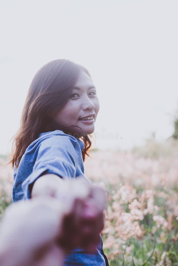 Följ mig, den lyckliga unga hipsterkvinnan som drar handen för grabb` s Hand in royaltyfri fotografi