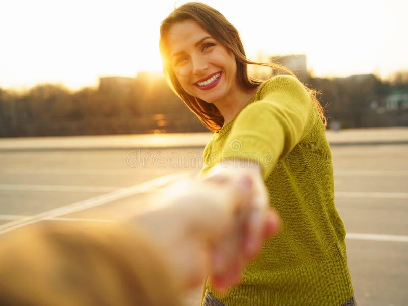 Följ mig - den lyckliga unga kvinnan som drar handen för grabb` s - handen - in - handen arkivbild