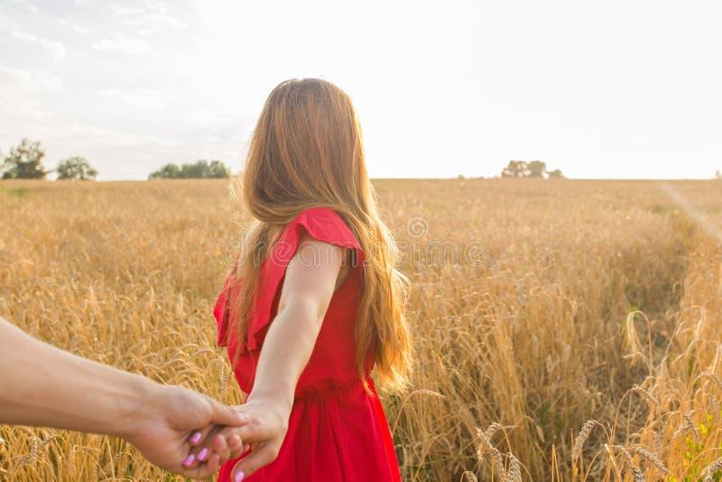 Följ mig, härliga håll för ung kvinna handen av mannen i ett vetefält royaltyfria bilder