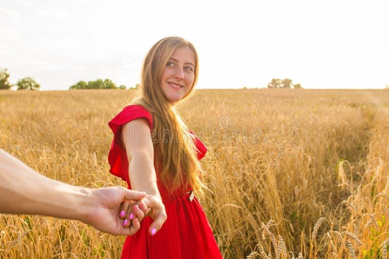 Följ mig, härliga sexiga håll för ung kvinna handen av en man i ett vetefält fotografering för bildbyråer