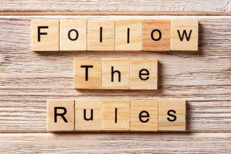 Följ regelordet som är skriftligt på träsnittet Följ reglerna smsar på tabellen, begrepp royaltyfri bild