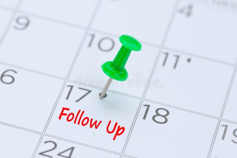 Följ upp skriftligt på en kalender med ett grönt pushstift för att påminna royaltyfri bild