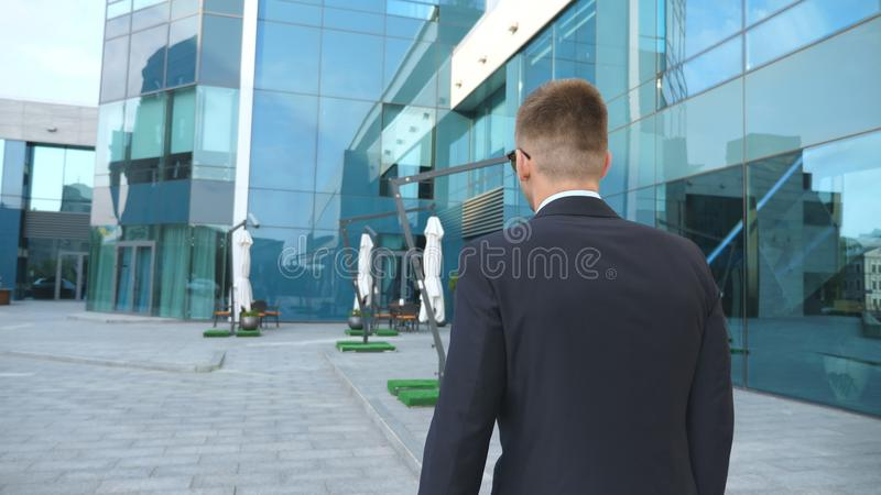 Följa till den unga affärsmannen med en portfölj som går nära modern kontorsbyggnad Affärsman, i att pendla för sunglass royaltyfri bild