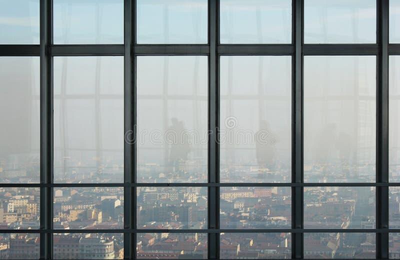 Fönster överst av en skyskrapa med en sikt av den Milan och folkkonturreflexionen royaltyfri foto
