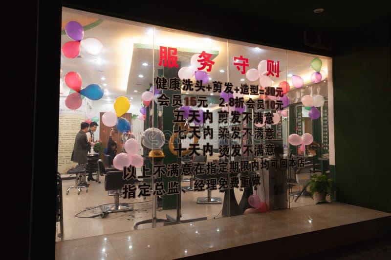 Fönster av den kinesiska frisersalongen på natten arkivbilder