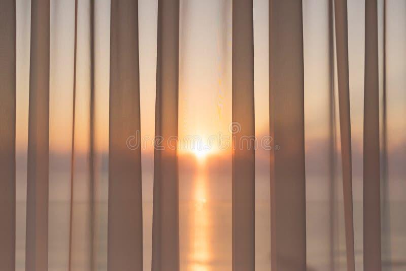 Fönster av en balkong med genomskinliga gardiner och sikt av det morgonsolen och havet Begrepp royaltyfri fotografi