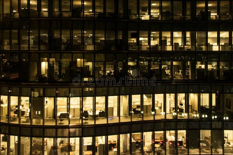 Fönster för gult ljus av en kontorsbyggnad på natten i den Boston sent - natten på arbete glass kontorsbyggnad för gardinvägg royaltyfri bild