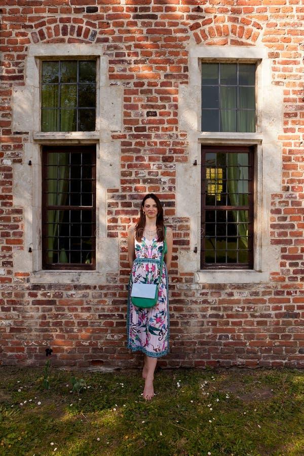 Fönster för vägg för brunettkvinna antikt, Groot Begijnhof, Leuven, Belgien royaltyfri foto
