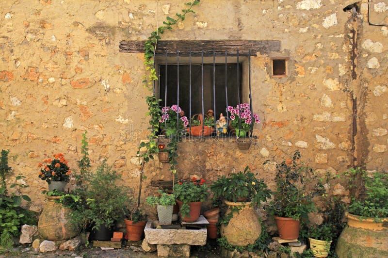 Fönster i det lantliga huset för sten med blomkrukor, Provence arkivfoto
