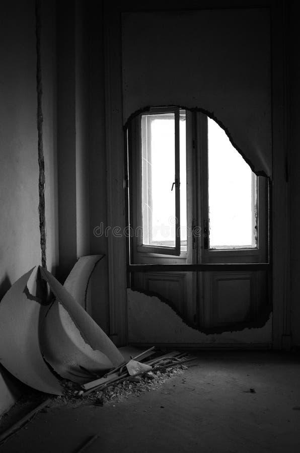 Fönster i ett övergett rum med att smula väggar arkivbild