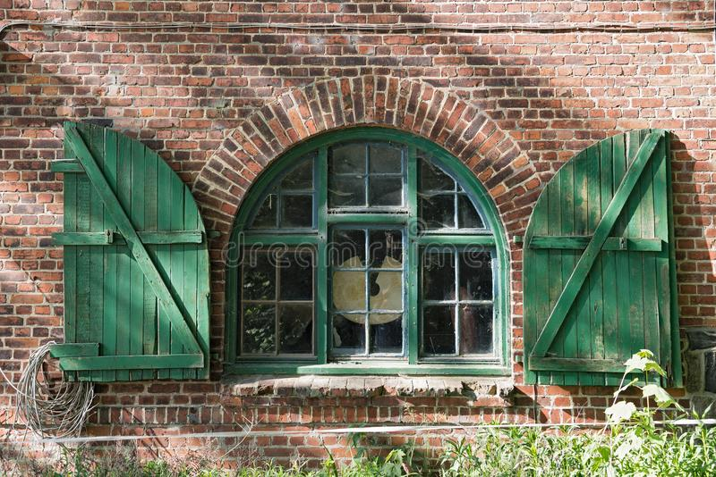 Fönster i ett tegelstenlantbrukarhem med slutare i Schleswig Holstein, Tyskland royaltyfri fotografi