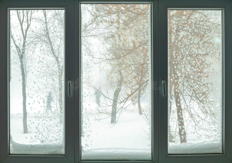 Fönster i rysslägenhet med snöhäftiga snöstormen och träd arkivfoto