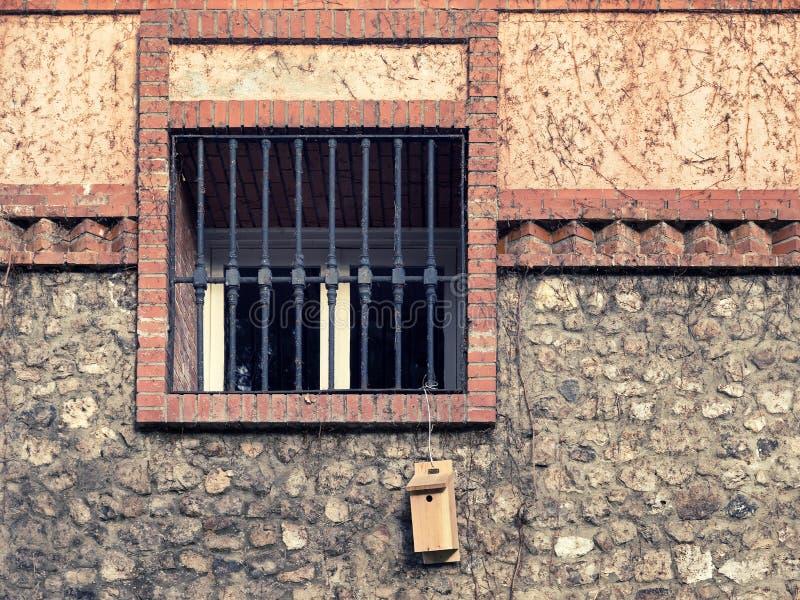 Fönster med det ron gallret på en lantlig fasad royaltyfria foton