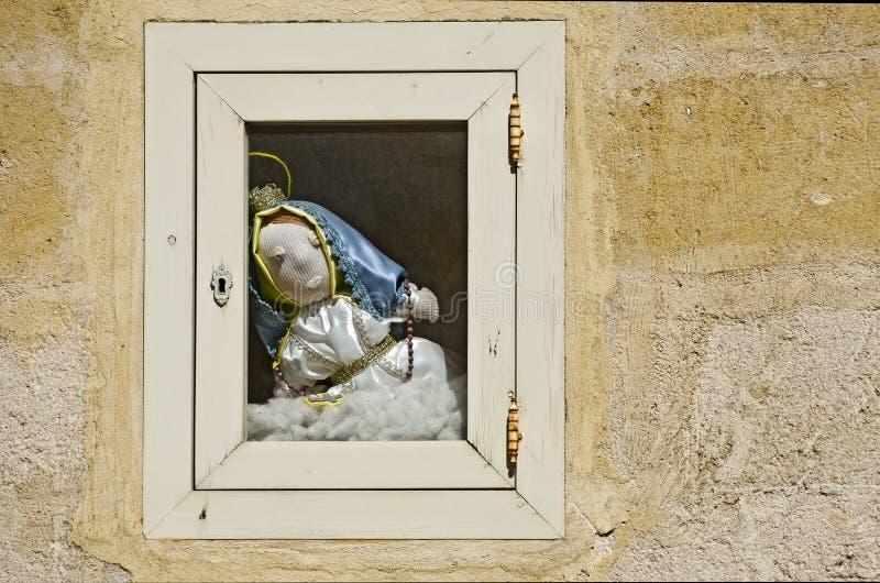 Fönster med en Madonna docka arkivbilder