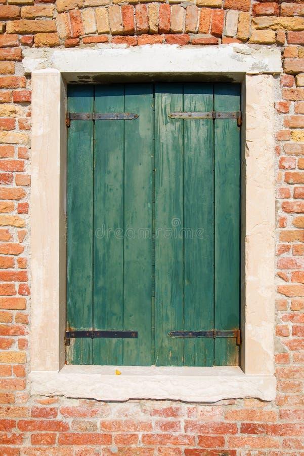 Fönster med gamla gröna träslutare i den sol- dagen för tegelstenvägg, Venedig arkivfoton
