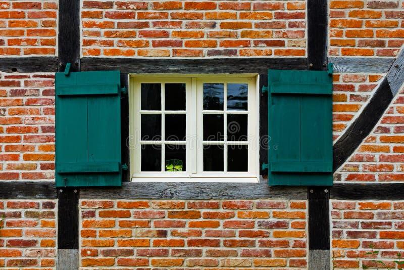 Fönster med slutare i tegelstenvägg av det halva timrade huset royaltyfri foto