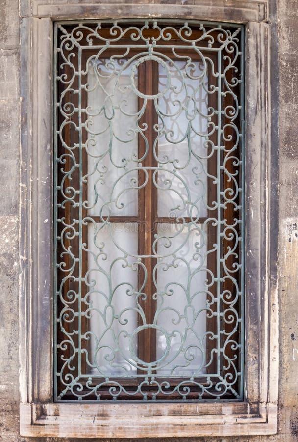 Fönster med smyckat metallgaller på en stenbyggnad royaltyfria bilder