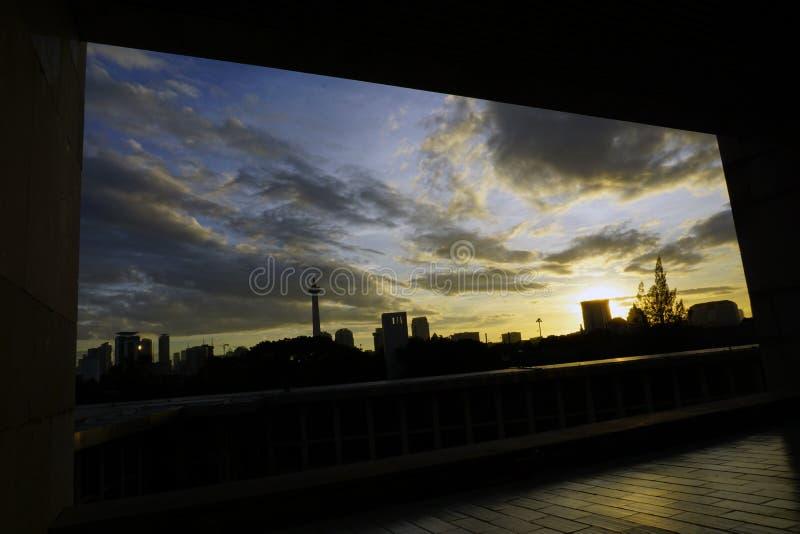 Fönster med tanke på staden under solnedgången royaltyfria bilder
