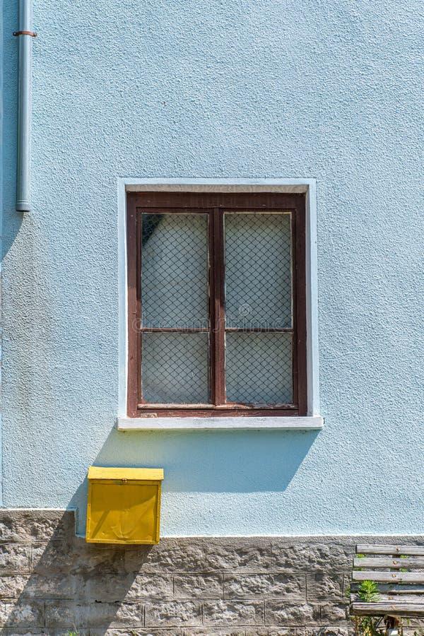 Fönster och en gul postbox på en blå vägg på ett hus arkivfoto