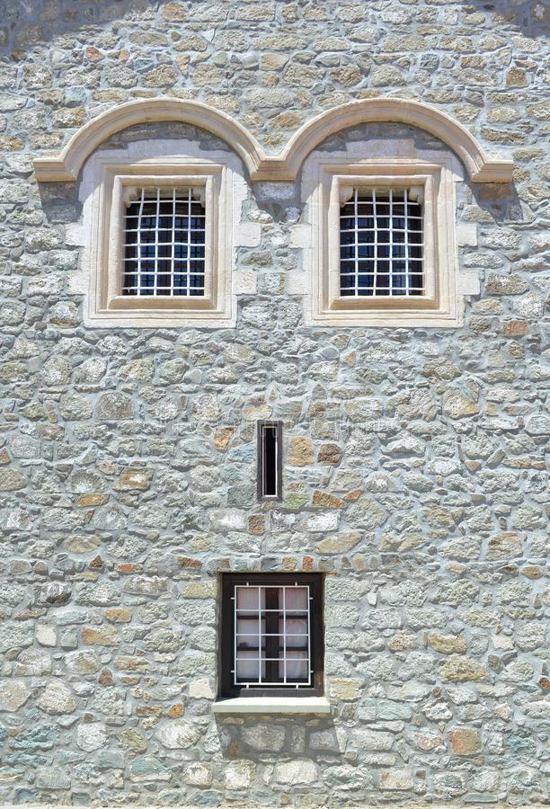 Fönster på en stenvägg av huset Tack vare ser fönsterläget, fasad som en mänsklig framsida royaltyfria foton