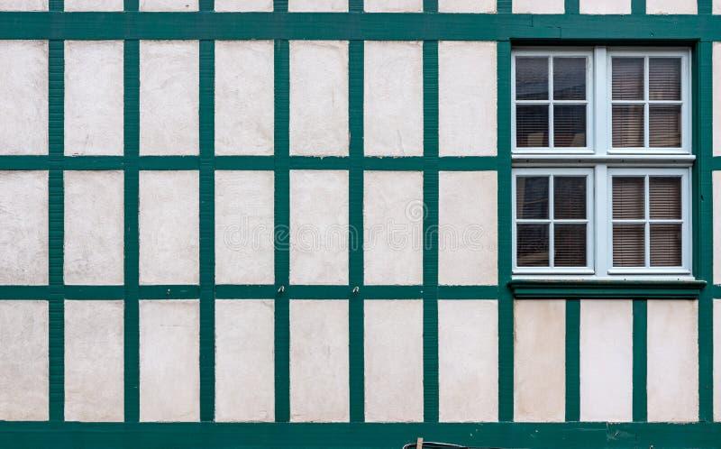 Fönster på en vit vägg med gamla trästrålar arkivbild