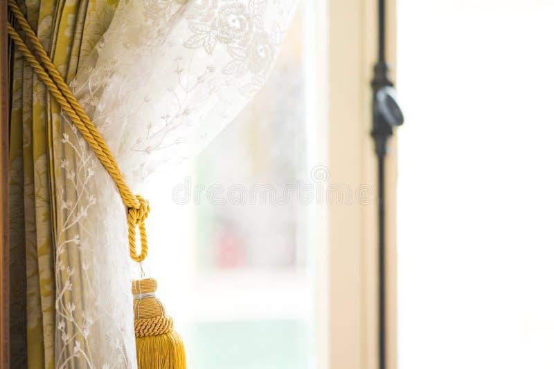 Fönstergardiner i huset utanför exponeringsglaset är den regniga dagen, hänger upp gardiner inregarnering i vardagsrum med sollju royaltyfri foto