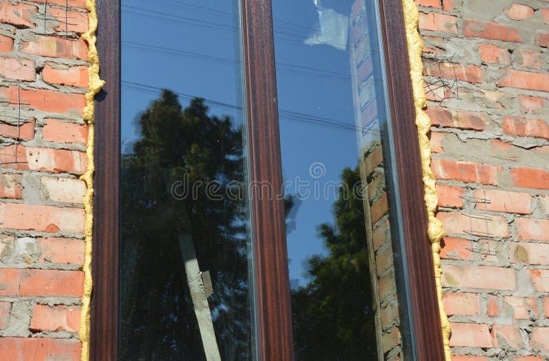 Fönsterisolering med skum på konstruktion för tegelstenvägg Isolera runt om öppningen med sprejskumisolering arkivfoto