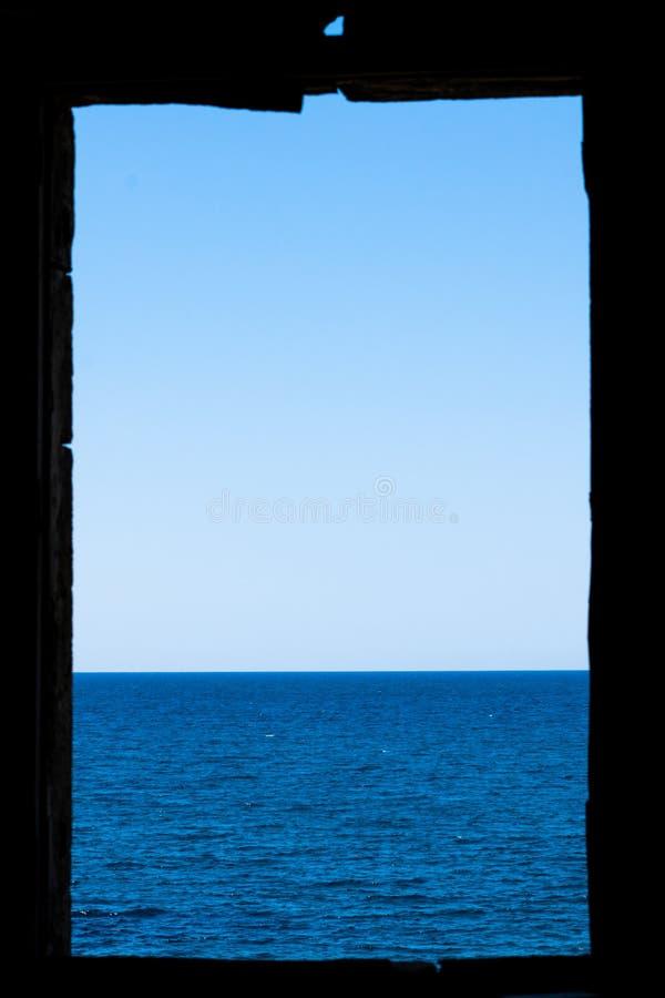 Fönsterramen fördärvar in på havet fotografering för bildbyråer