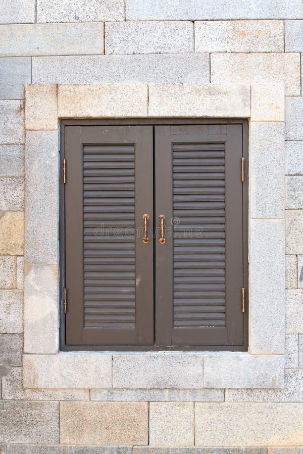 Fönstertappning på tegelstenväggen arkivfoto