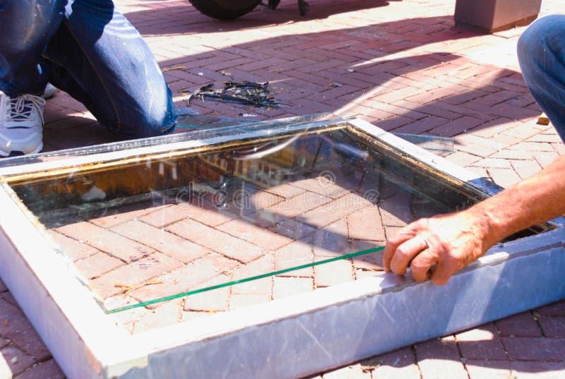 Fönstertillverkare på arbete efter tung storm royaltyfri bild
