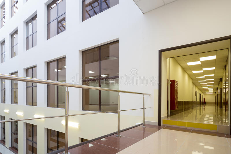 Fönstren av kontor och en lång korridor i modern härlig affärsmitt royaltyfria bilder