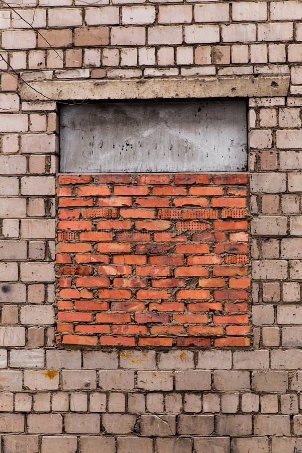 Fönstret brickeds upp Fönstret är lagd tegelsten Grå tegelstenvägg med ett fönster som läggas med röd tegelsten Fönstret är halva arkivfoto