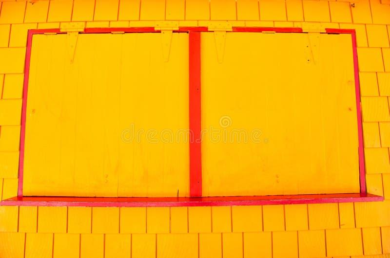 Fönstret med metall stänger med fönsterluckor på den gula väggen i philipsburg, sint maarten Fasaden av stängt shoppar, små och m royaltyfri foto