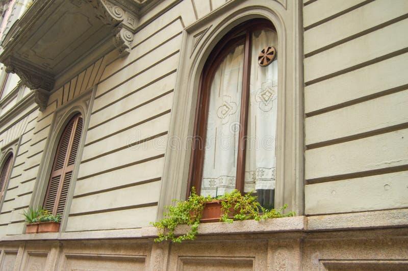 Fönstret på väggen av ett stenhus som dekoreras med, snör åt gardinen, tappningstil, Milan, Italien, 06 Oktober 2018 arkivfoto