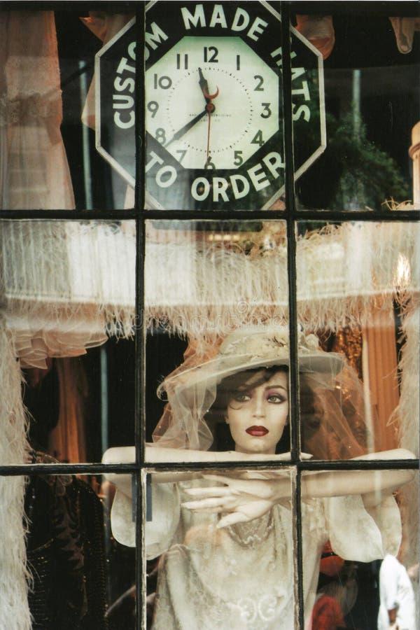 Fönstret shoppar, snör åt en docka med klänningen och den speciala hatten arkivfoto