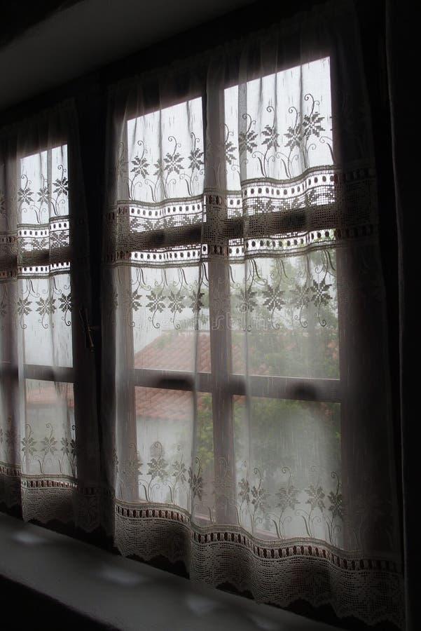 Fönstret snör åt gardinen arkivbild