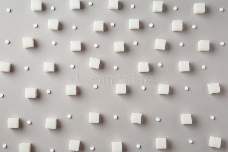Förädlade kuber för vitt socker med steviapiller på grå bakgrund arkivfoto