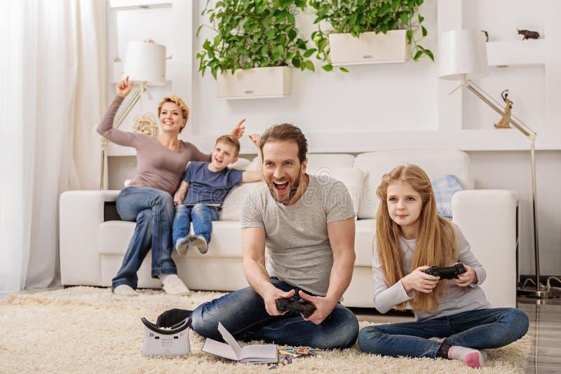Förälder och barn som spelar videospelkonsolen arkivfoton