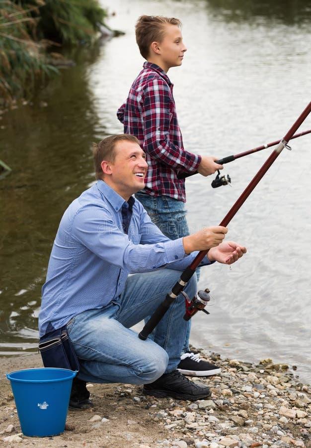Förälder och pojke som tillsammans fiskar på den sötvattens- sjön royaltyfria bilder